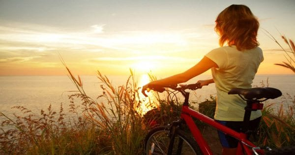 blog picture of lady bike riding in the hills looking out at the sunset