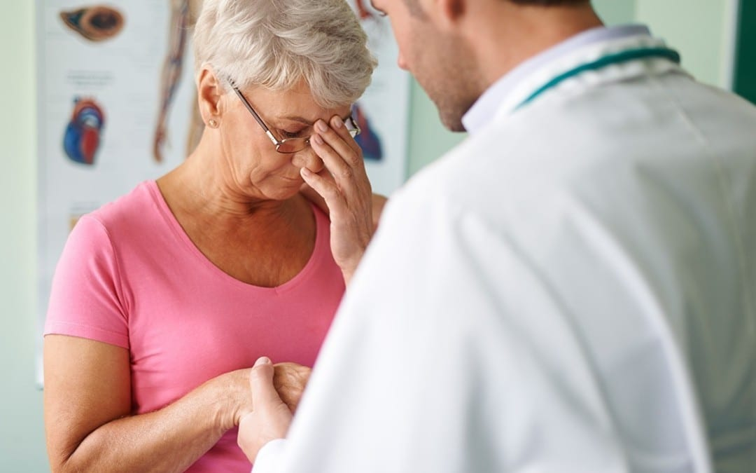 Older woman being diagnosed for BPPV by a doctor.