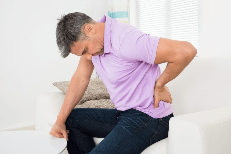Image of a man holding his back due to sciatica and radicular back and leg pain.