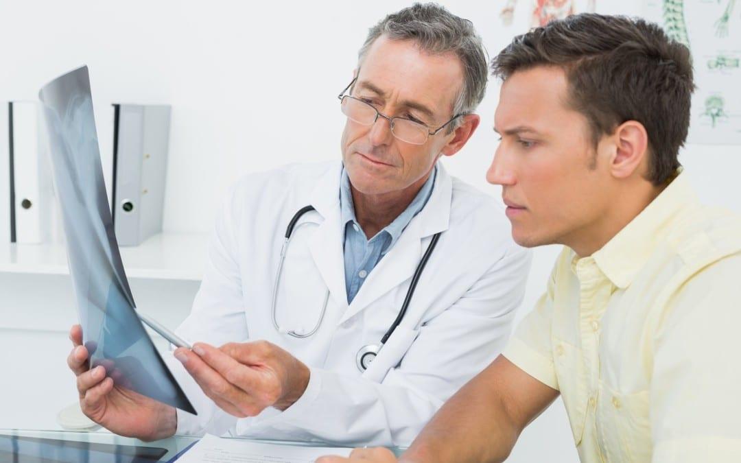 Doctor explains arthritis diagnosis on patient's x-rays.